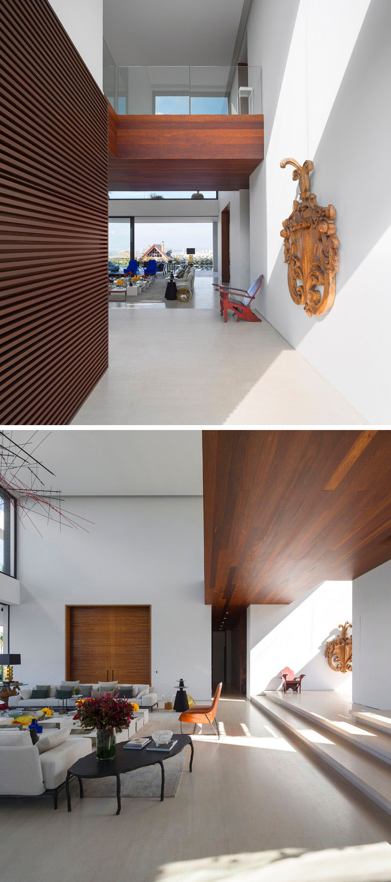 The entry way of this home reveals a double height ceiling, white walls and wood detailing.