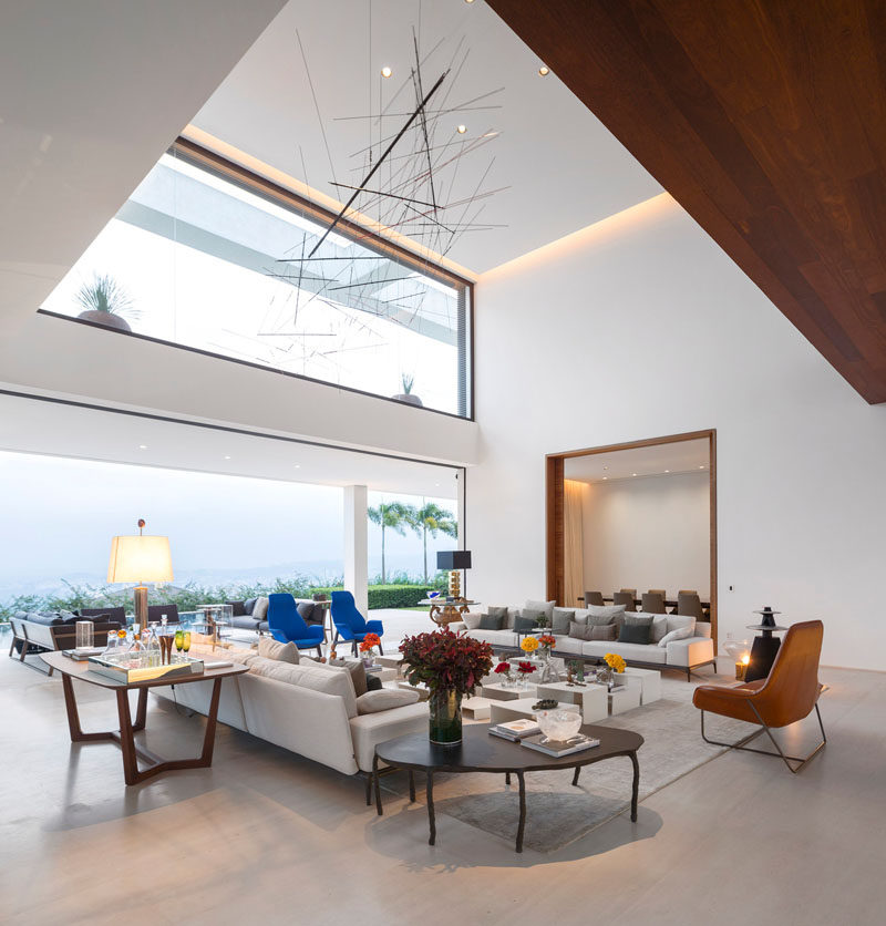 This living room has a large delicate sculptural piece hanging above it.