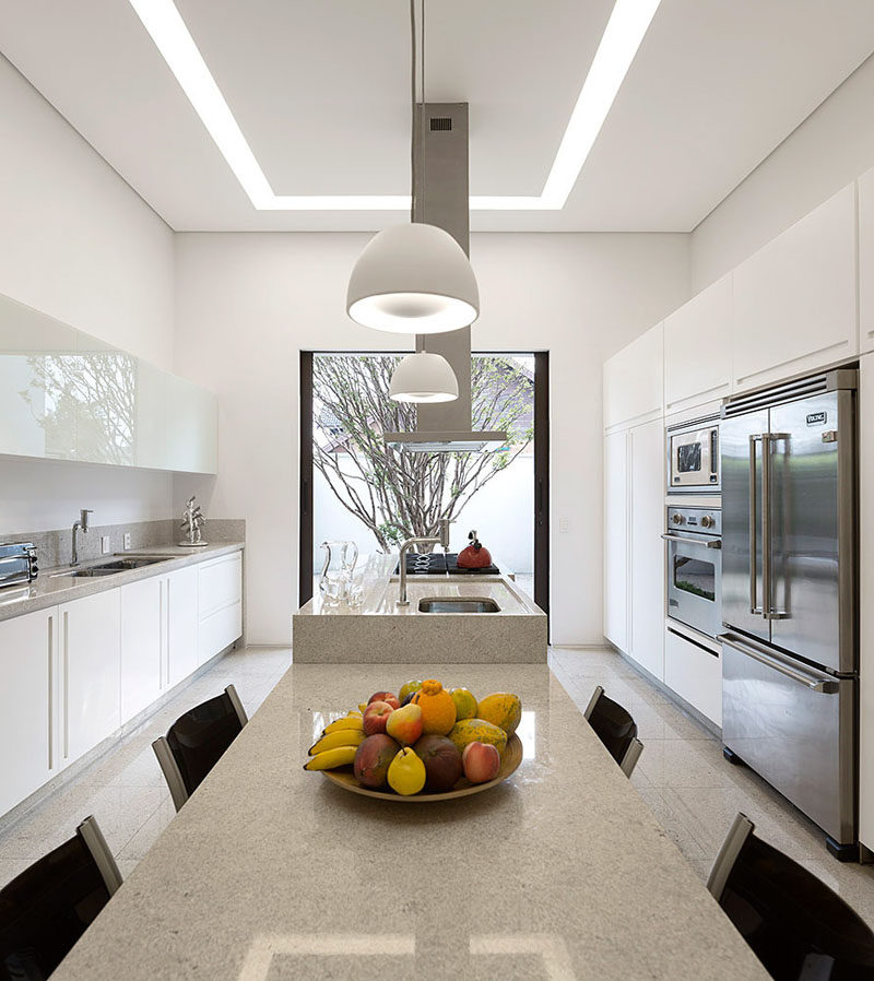 This kitchen, with its white cabinetry, has a large picture window at the end that perfectly frames the tree outside, and also lines up with the kitchen island.