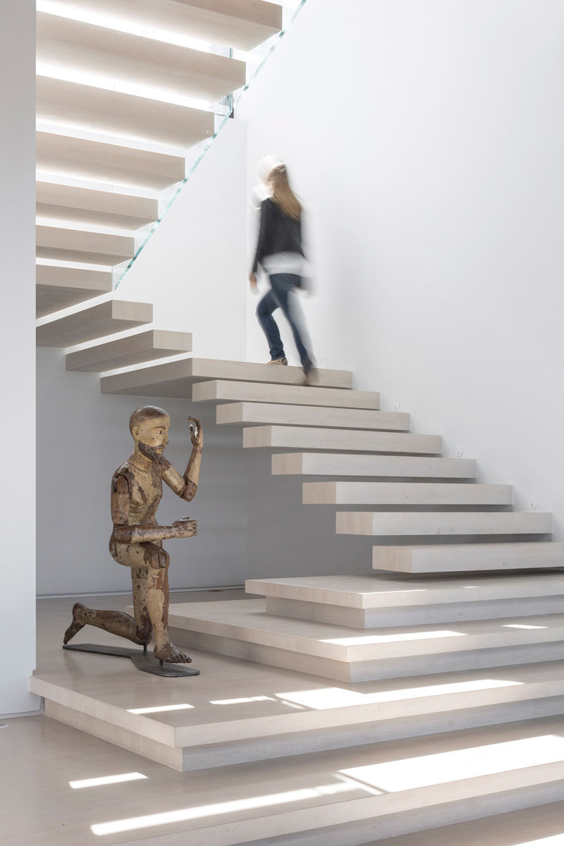 Light colored stone floating stairs with a space for a sculpture, lead you upstairs in this home.