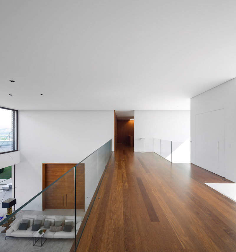 This walkway with wooden floors and glass railings, provides views of the living room below.