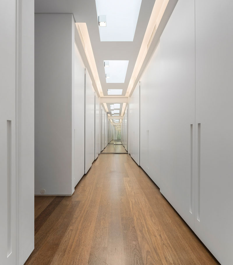 This walk-in closet has a wooden floor, and storage from the floor to the ceiling. There is also plenty of lighting and a mirror helps to make it appear as larger than it is.