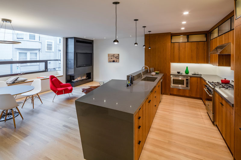 This open plan living, dining and kitchen area, has a fireplace and tv tucked into the corner, and a U-shaped wooden kitchen with gray countertops.