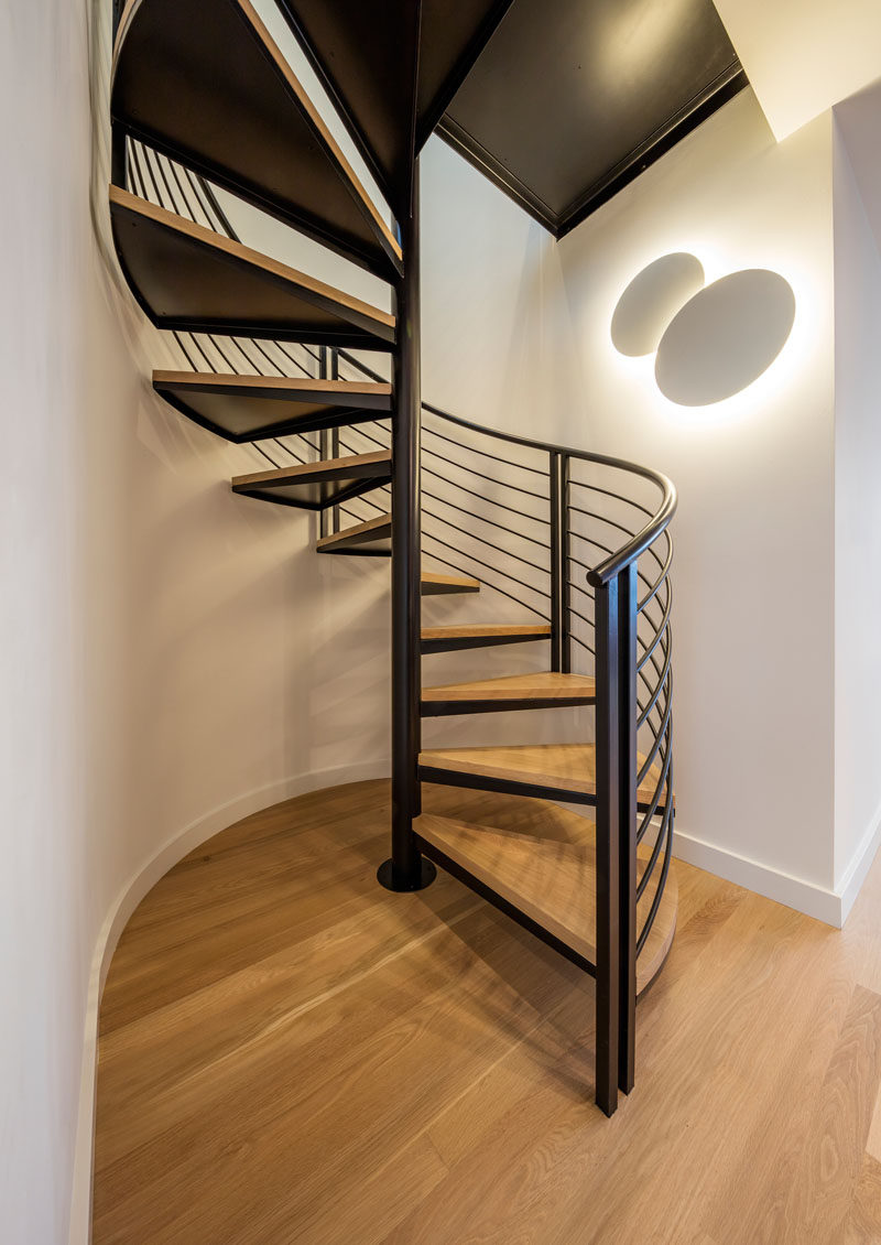 Black and wood spiral stairs are in direct contrast to the white walls.