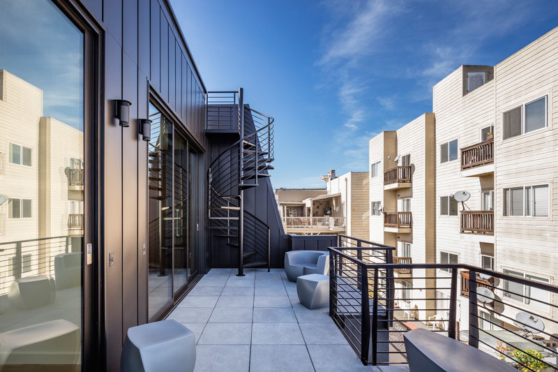 This outdoor balcony has various spaces for relaxing, and spiral stairs that lead to the rooftop.