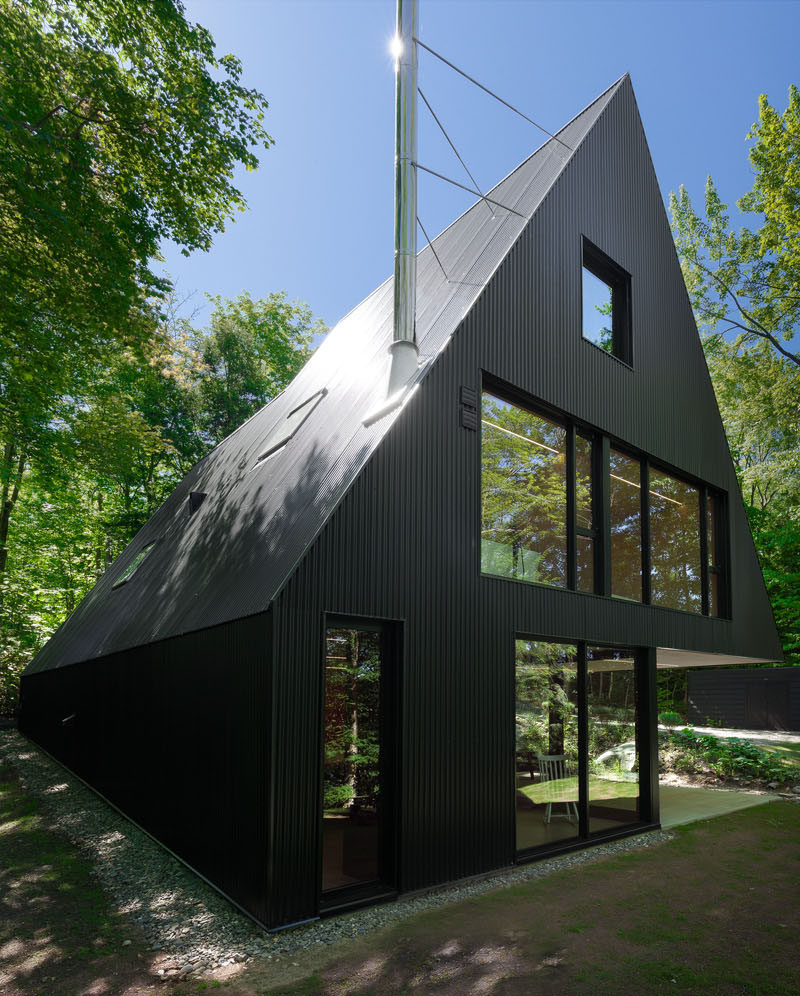 This black cottage with a sloping roof line, is surrounded by a Hemlock forest in Quebec, Canada.