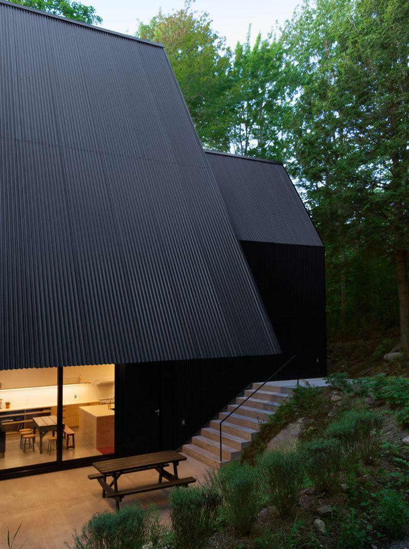 This black Canadian cottage has an overhang that covers the terrace below.