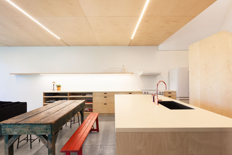 This kitchen has been kept simple, and a shelf along the wall hides additional lighting.