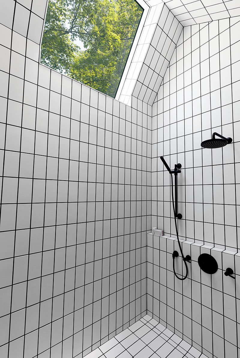 This bathroom has white tiles, but they have used black grout to match the shower heads and taps. There's also a skylight to provide extra light to the bathroom.