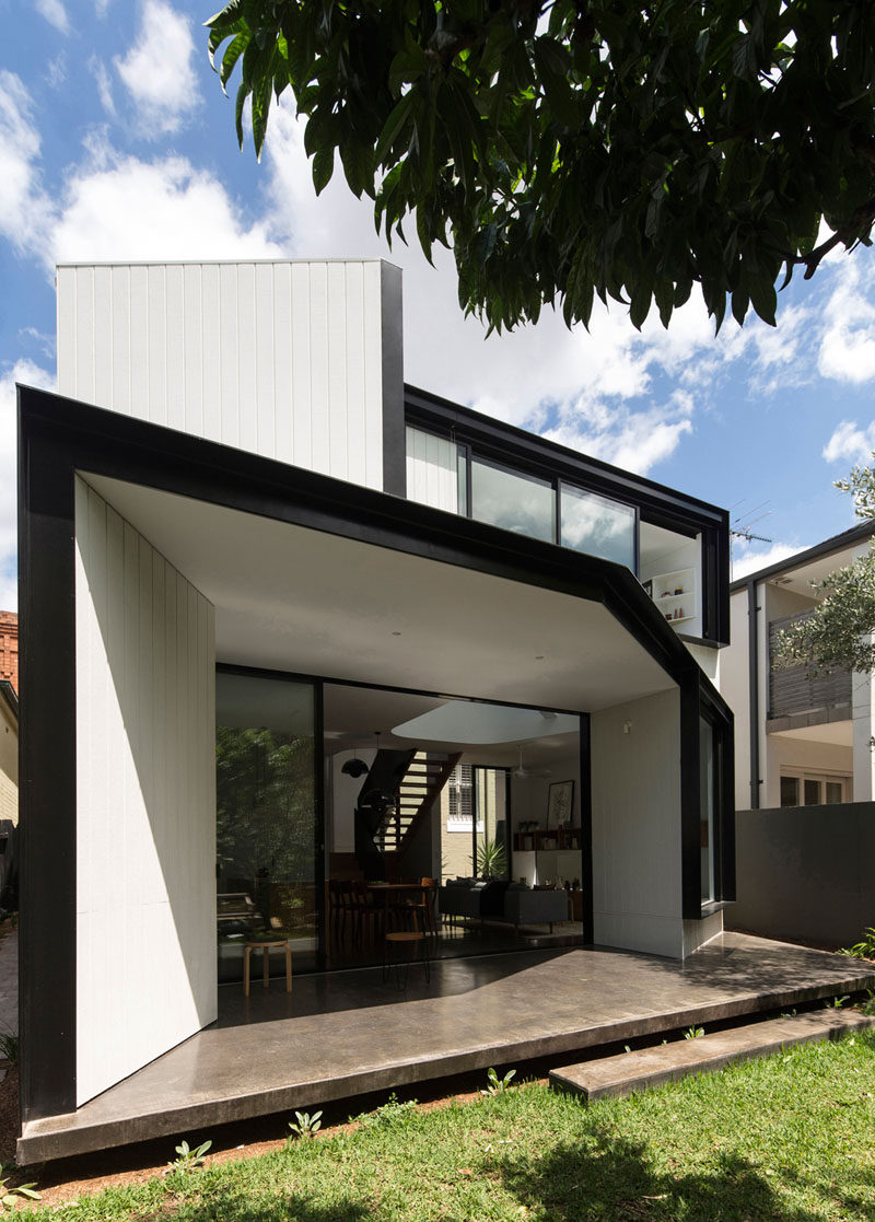 Black frames and concrete patio contrast the white siding and interior of this house extension in Sydney, Australia.