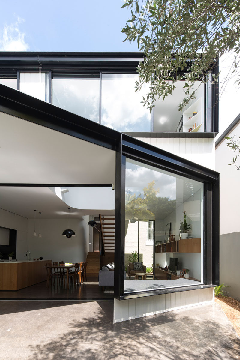 This house extension has a large window with black frames, as well as a window seat built-in on the inside.