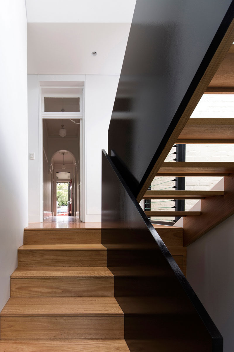 Wood stairs with a black safety railing and white walls.