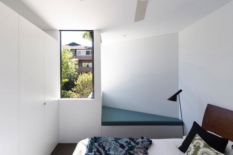 This bedroom has a small angled reading nook with views of the backyard.