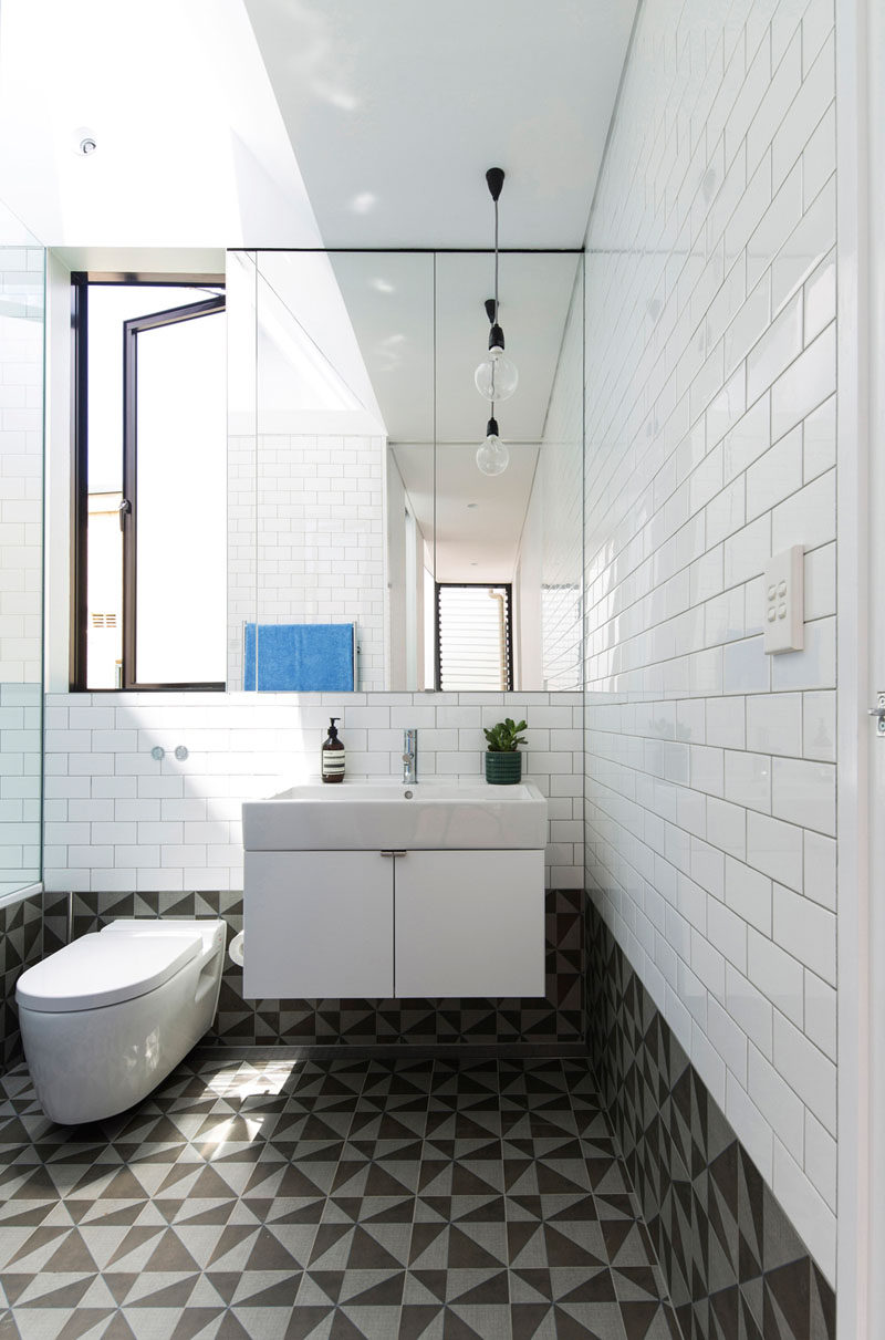 In this bathroom, white tiles match the white walls in the rest of the home, while the floor and lower portion of the walls are a bold graphic tile.