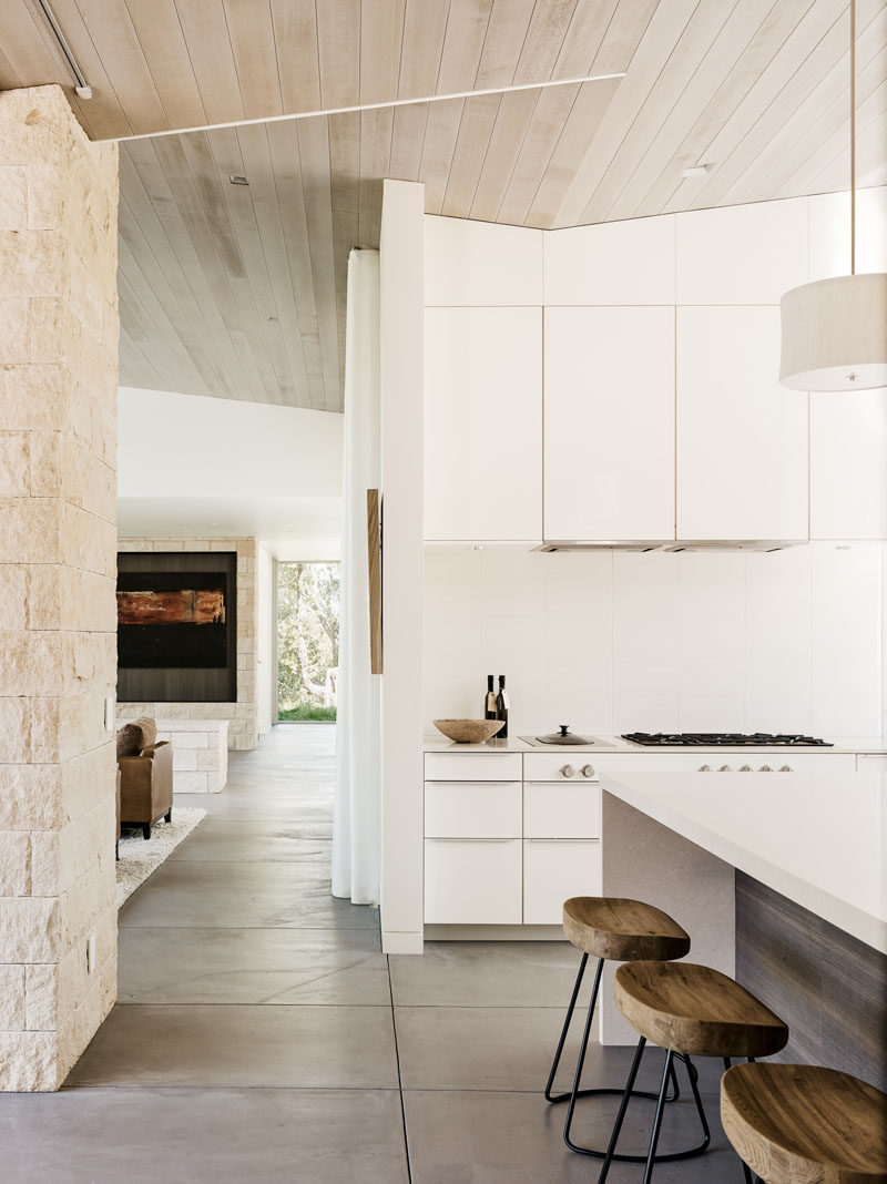 This kitchen is full of white cabinetry, has a large kitchen island with seating, windows that face a courtyard and cedar-clad ceilings.