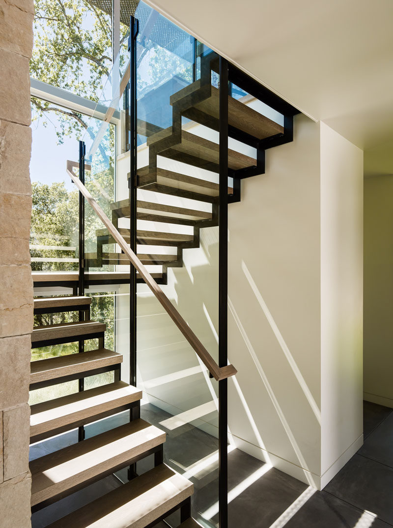 Wood and steel stairs lead you to the upper floor of this home, with large windows flooding the area with sunlight.