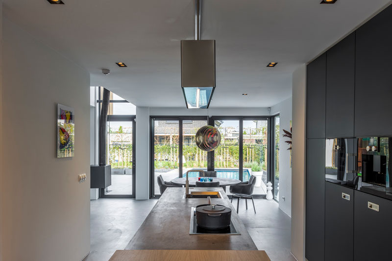 This kitchen and dining area are filled with natural light from the floor-to-ceiling windows.