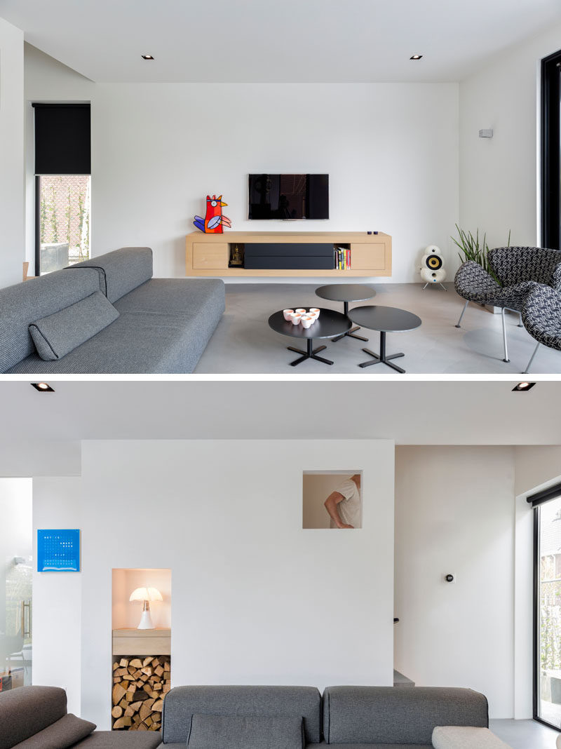 This living room has been kept minimal in its design, with a floating unit attached to the wall. There's also a built-in cubby for wood storage.