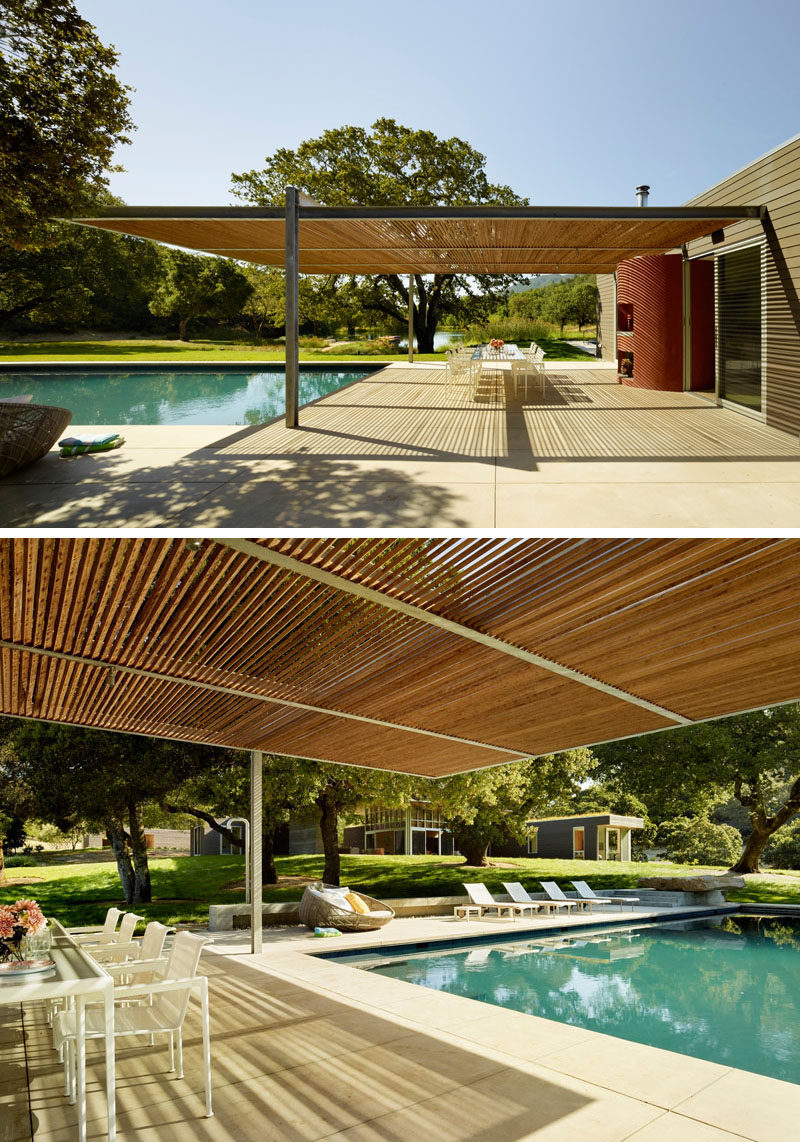 This swimming pool is surrounded by a shaded outdoor dining area, and a space for lounging in the sun.