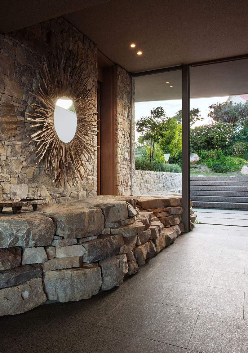 This home has a stone wall that carries from the outside through to the entryway, and a large mirror helps to reflect light.