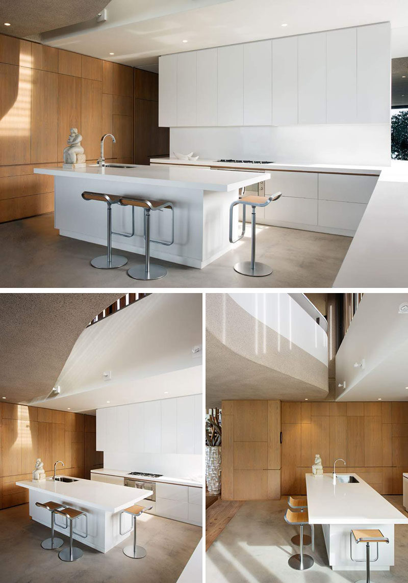 In this kitchen, the color palette is super simple, just white cabinets with touches of wood in a wall of cabinets and the counter stools. A minimal look in the kitchen has been achieved by having cabinetry without hardware.