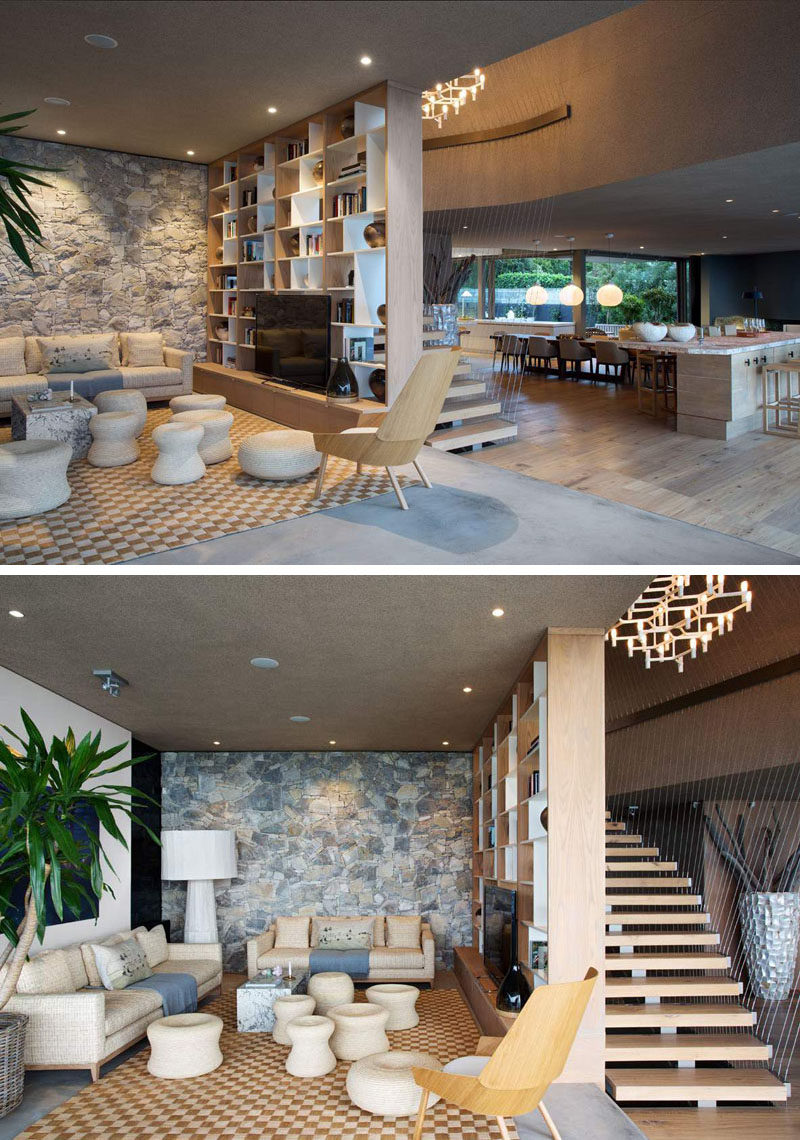 This living room has a stone feature wall and a bookshelf that separates the room from the stairs.