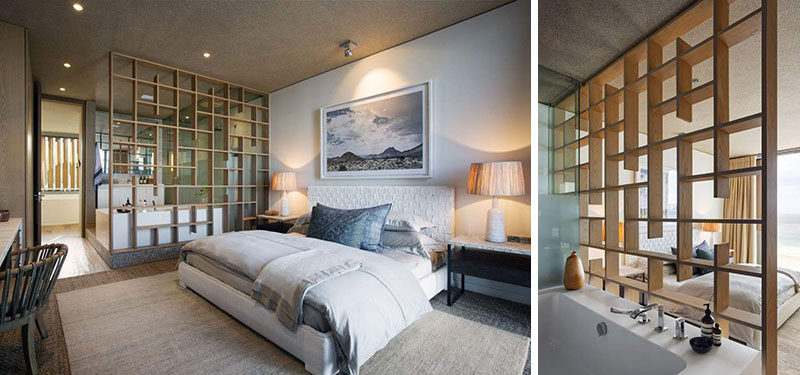 In this bedroom, there is a custom-designed wooden partition separating the bedroom from the ensuite bathroom.