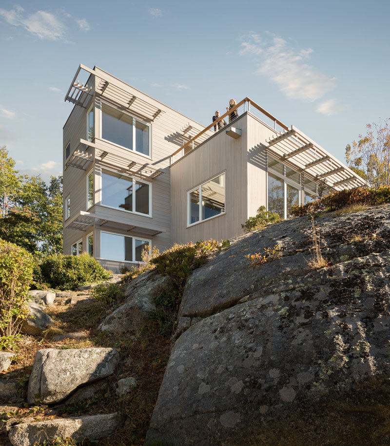 This home in Maine, USA, sits on top of granite rock and is clad in white cedar boards and zinc panels.