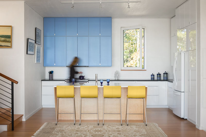 This kitchen has pops of blue in the cabinets and yellow in the stools to add some colour to the overall white and wood color palette.