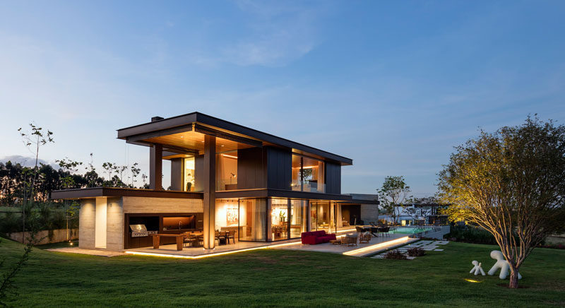 This contemporary farmhouse in São Paulo, Brazil, takes advantage of the views and outdoor lifestyle, with a large backyard, swimming pool, outdoor kitchen and dining area, as well as an outdoor lounge.