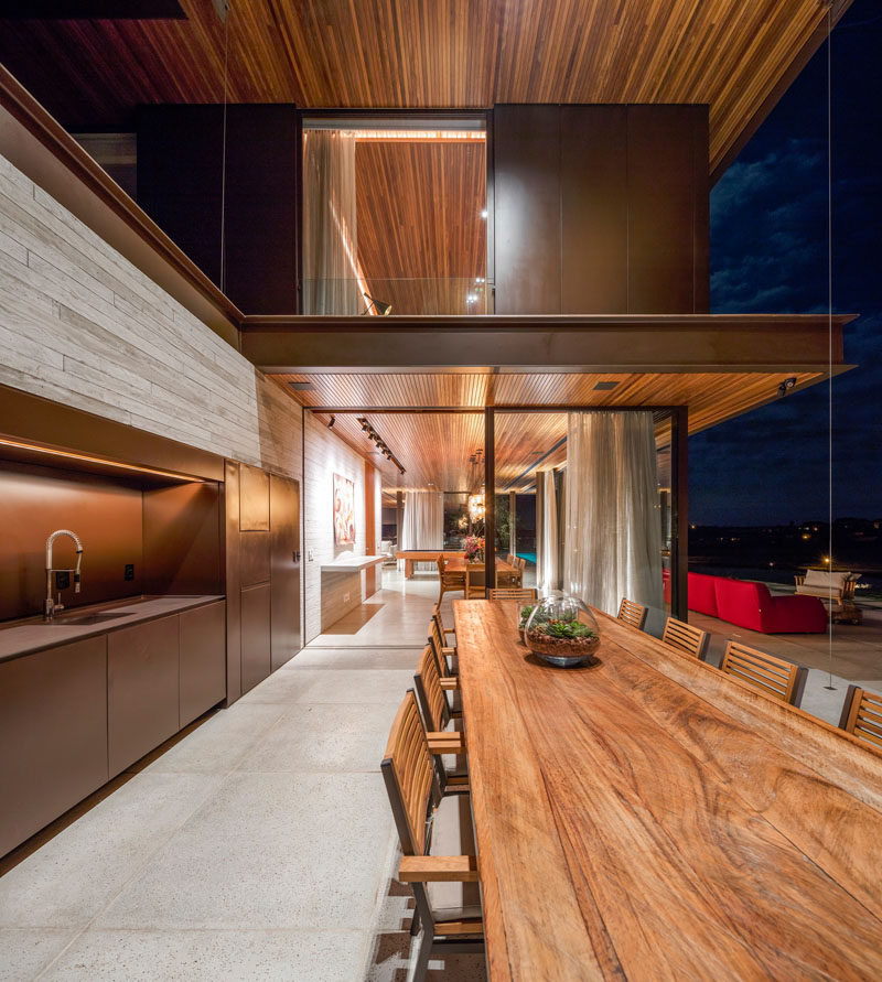 This Brazilian home has an outdoor kitchen and large wooden dining table, perfect for outdoor entertaining.
