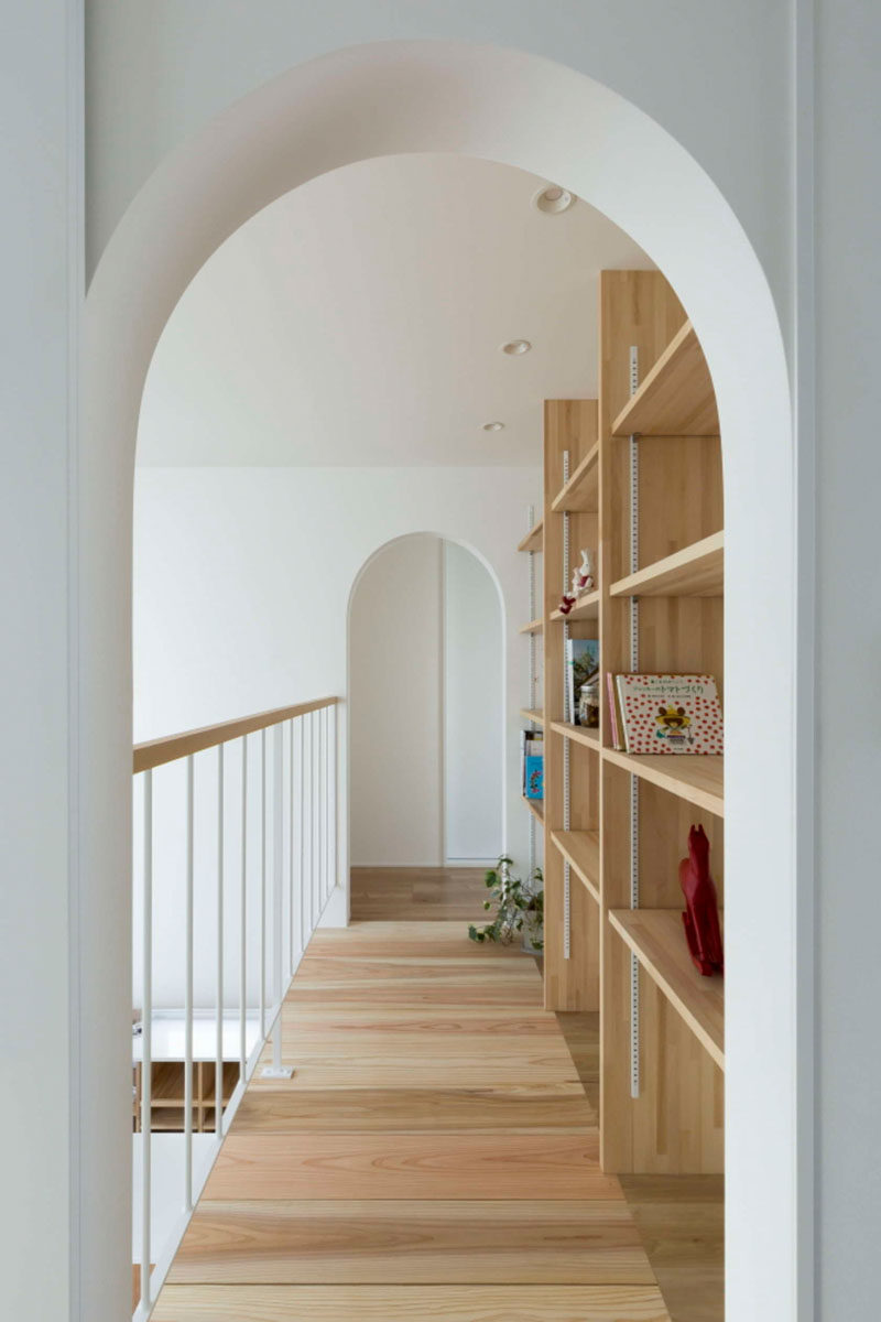 White arched doorways are located on either side of the walkway with a bookshelf on one side, and a view of the lower level of the home on the otherside.