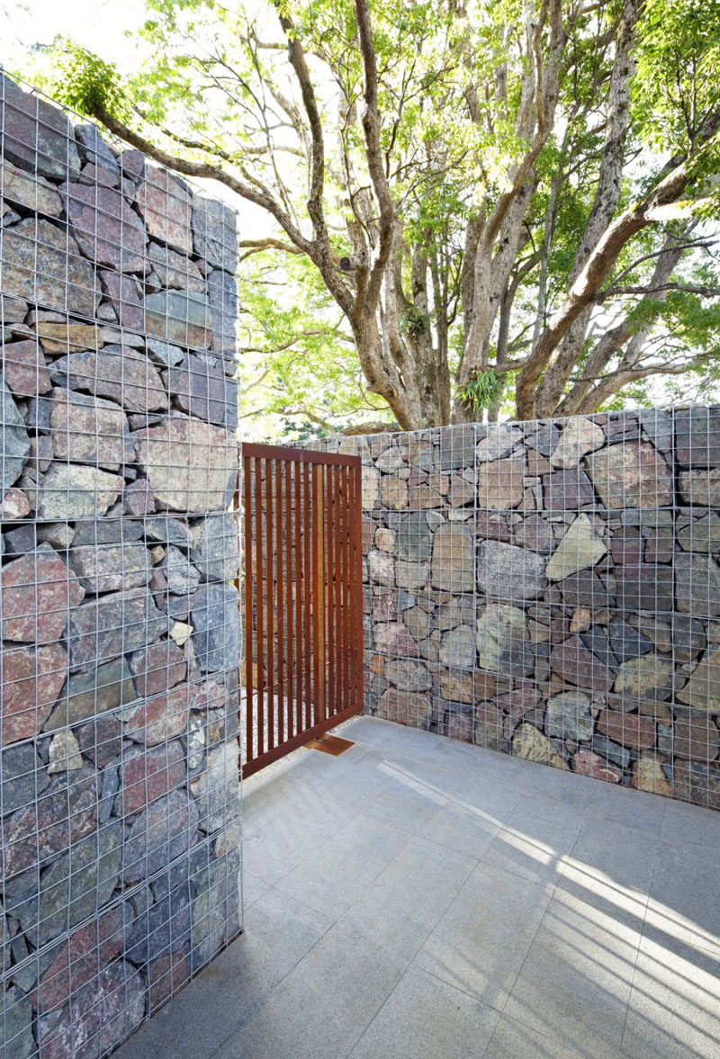 A gabion is a cage filled with rocks, concrete scraps, or really anything you can fit into the wire cage. #Gabion #LandscapingIdeas #FenceIdeas #ModernFence #Architecture #Landscaping