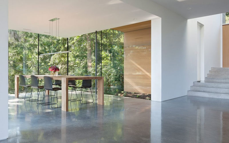 The glass walls that surround this dining room allow for plenty of natural light to flood the room, and at the same time, they provide amazing views of the forest and ocean in the distance.