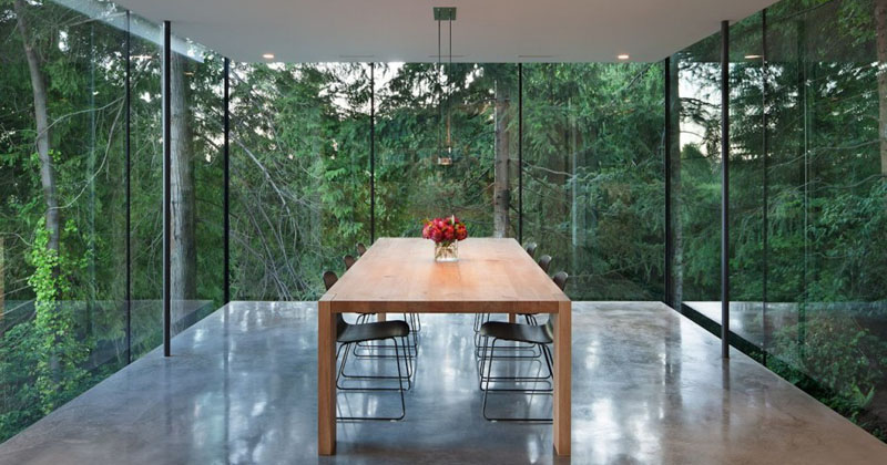A Dining Room Surrounded By Glass Hangs Off The Side Of This House