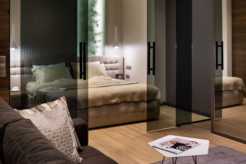 These tinted sliding glass doors define the bedroom area and allow light to carry through to the space.