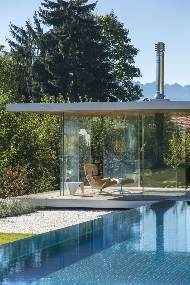 This contemporary glass pool house has uninterrupted views, sliding doors on all sides, a hanging fireplace and a hidden fridge in the floor.