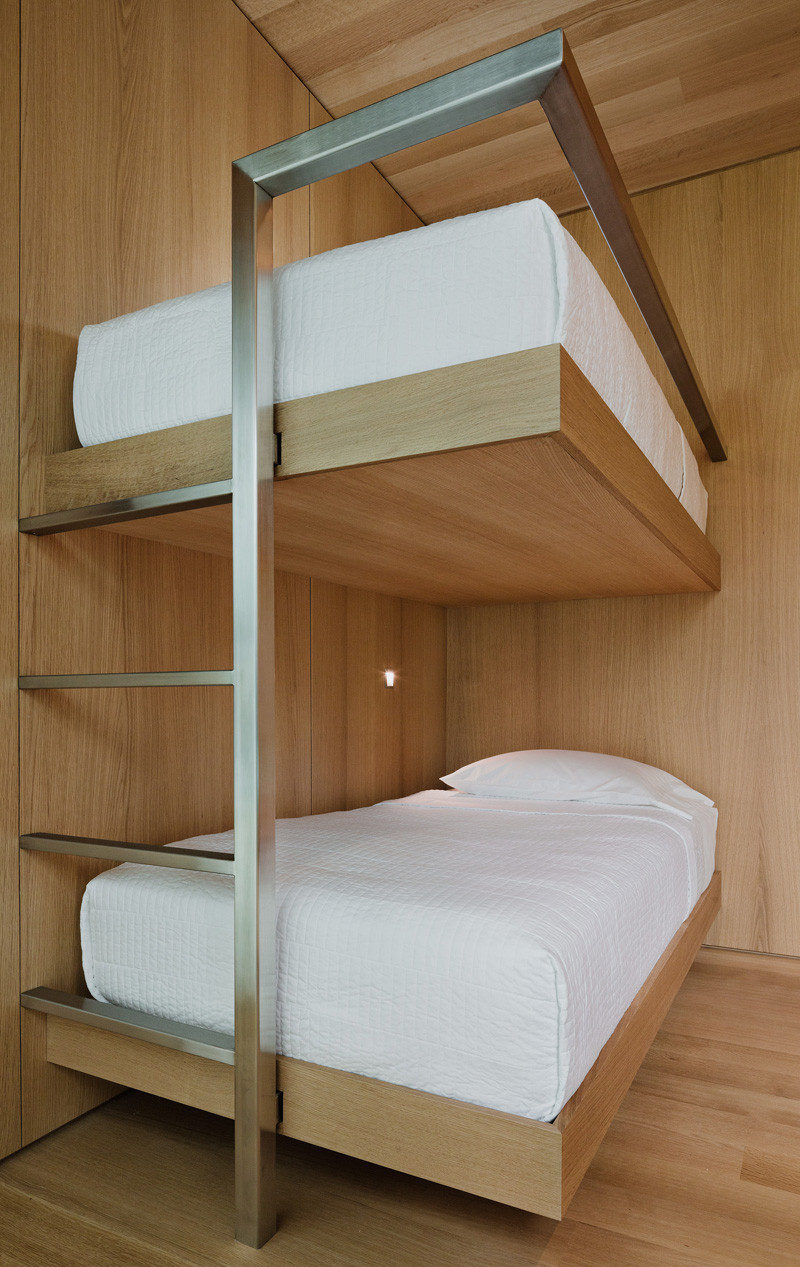 Wood and stainless steel bunk beds with white bedding.