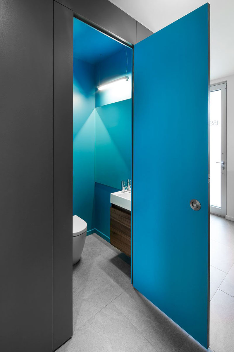 The door of this bathroom opens up to reveal a bright blue interior.