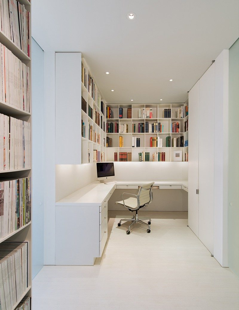 This home office with plenty of storage is in a white themed apartment in Washington DC.