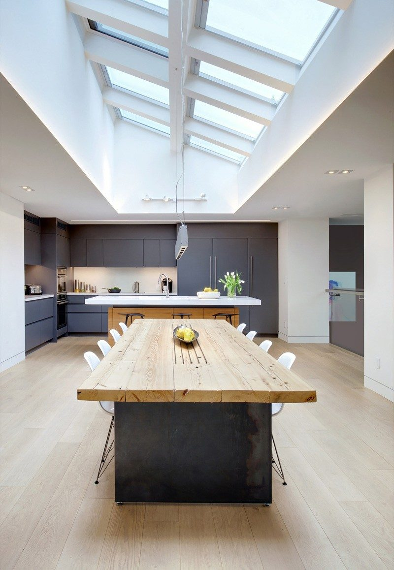 This home features a large wood and steel dining table with the ceiling covered in skylights.