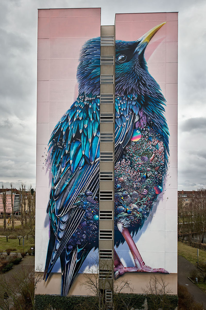 This large colorful mural of a bird can be found on the side of a building in Germany.