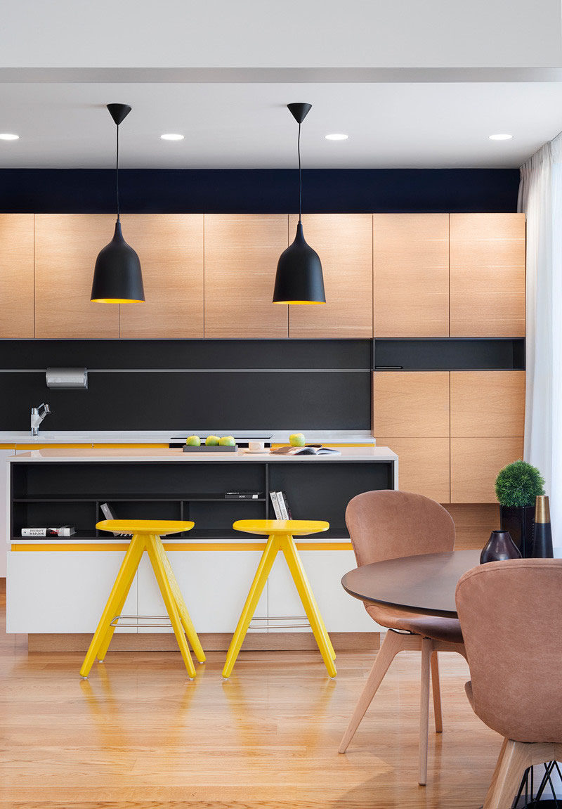 Sunny pops of yellow are found throughout this black and wood kitchen.