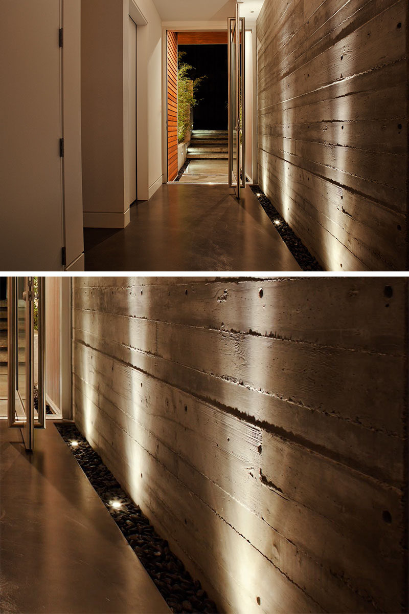 7 Interiors That Use Dramatic Uplighting To Brighten A Space // The strip of pebbles and lights that run along the side of the wall of the entry way in this house, uniquely welcomes people into the home and helps the texture of the concrete wall stand out.