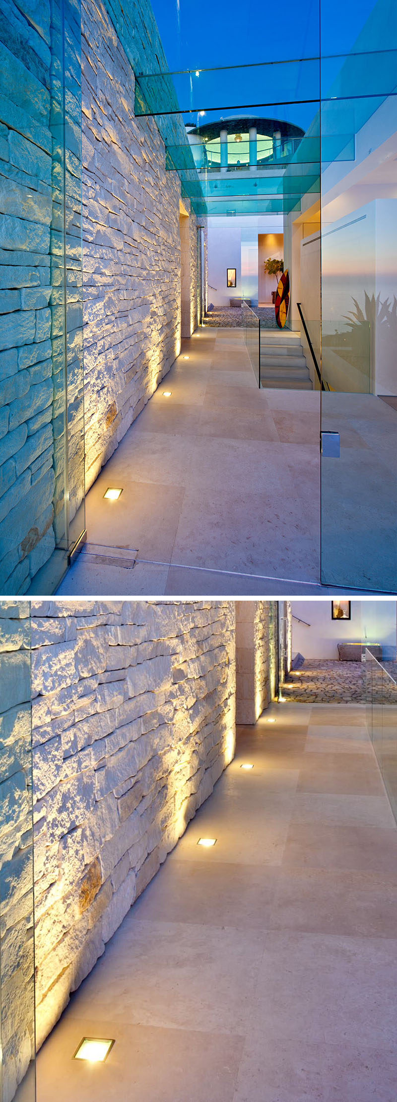 7 Interiors That Use Dramatic Uplighting To Brighten A Space // Warm lights run along the bottom of the entry way wall and highlight the texture of the stones used in the wall.