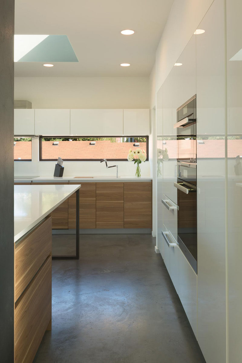 12 Inspirational Examples Of Letterbox Windows In Kitchens // The horizontal letterbox windows in this Seattle home brighten the space, and because they're at roof level of the houses around them, allow the kitchen to be kept somewhat private from the rest of the neighborhood.