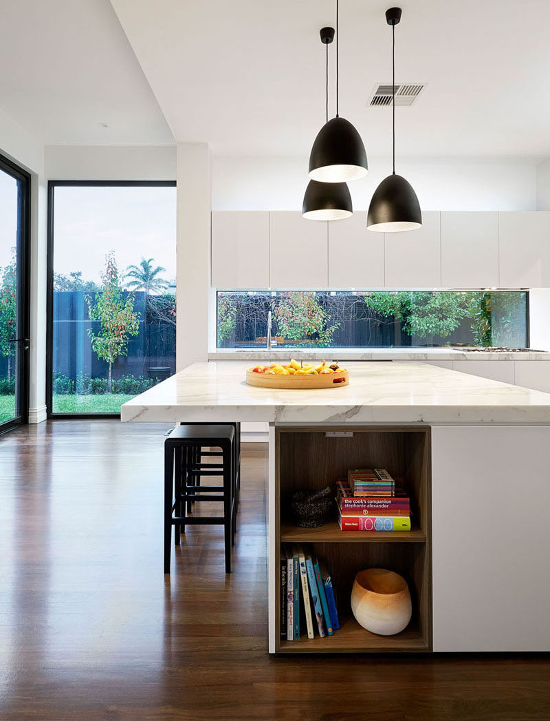 12 Inspirational Examples Of Letterbox Windows In Kitchens // White cabinetry, white walls, and a marble countertop, all partnered with the long letterbox window work together in this kitchen to make it super bright and welcoming.
