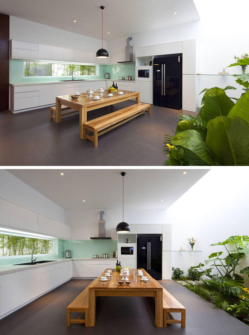 12 Inspirational Examples Of Letterbox Windows In Kitchens // The letterbox window in this kitchen breaks up the blue glass backsplash, provides a view of the bamboo shoots out in the yard and brightens up the entire kitchen.