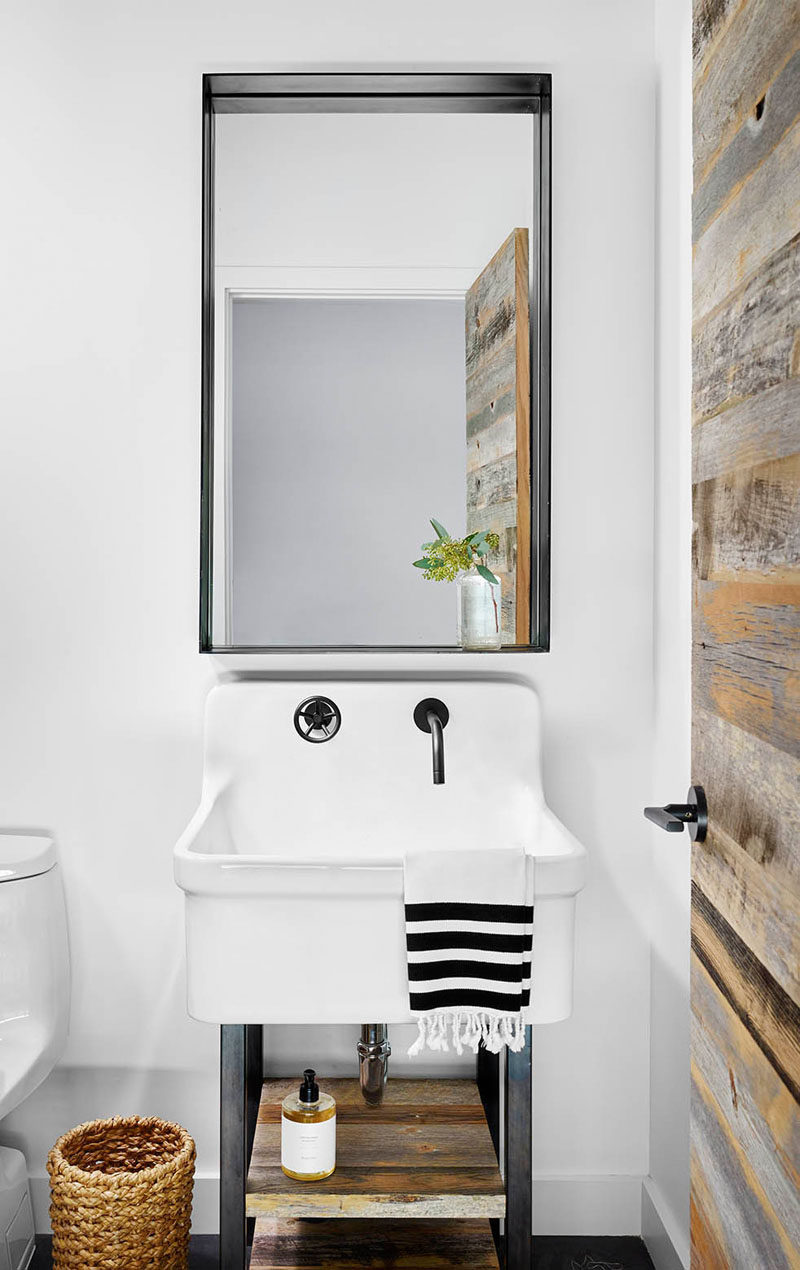 13 Ideas For Creating A More Manly, Masculine Bathroom // A reclaimed wood door with matching shelves attached to the white sink, make this bathroom the perfect amount of manly rustic and clean modern.