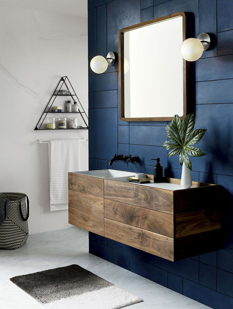 13 Ideas For Creating A More Manly, Masculine Bathroom // A dark blue accent wall and elements of dark wood and metal add an outdoorsy and masculine feel to this bathroom without making it feel dark or uninviting.